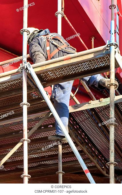 Scaffolder, wearing a safety harnass, climbing up an unfinished scaffold around a huge, industrial structure