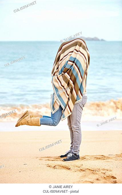 Romantic young couple covered in blanket on beach, Constantine Bay, Cornwall, UK