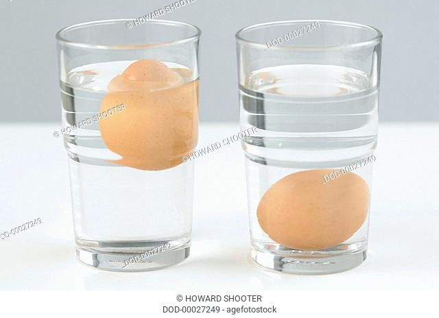 Two eggs in two glasses of water, one floating near the surface