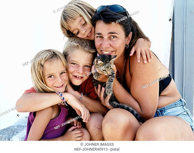 Portrait of mother with daughters and kitten