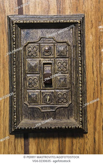 Close-up of On and Off electrical wall switch framed by a carved wooden plaque inside an old 1807 Canadiana style fieldstone home