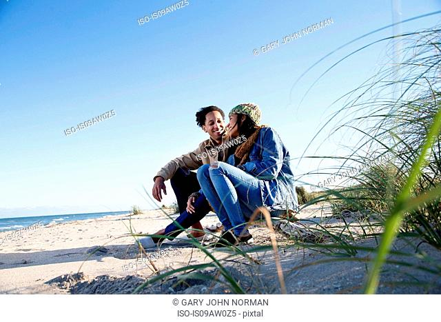 Young couple relaxing on beach, face to face, smiling