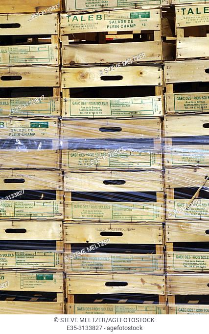 Stacks of wooden fruit crates at a fruit stand
