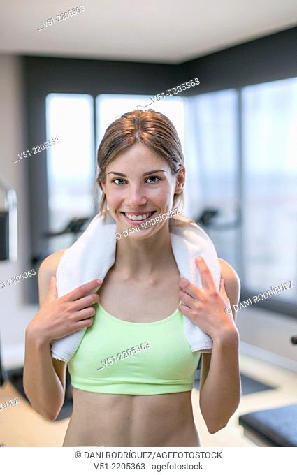 Portrait of a young woman in fitness center smiling at camera
