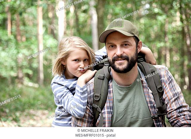 Portrait of smiling father and daughter in forest