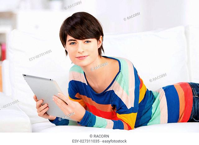 Woman holding a tablet relaxing on a sofa lying on her stomach in a colourful striped outfit