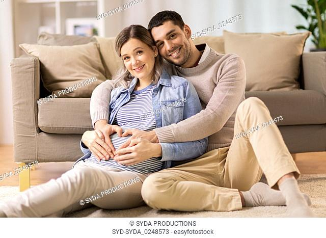 man with pregnant woman making hand heart at home