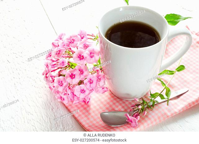 Morning coffee or cup of tea with pink flowers on wooden white rustic table. Selective Focus