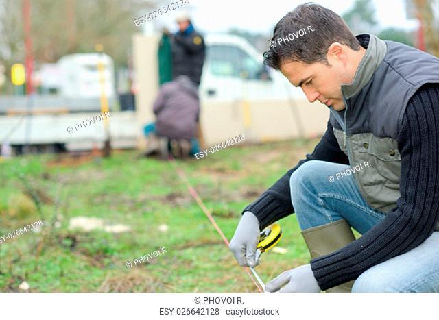 Builder taking measurements in the garden