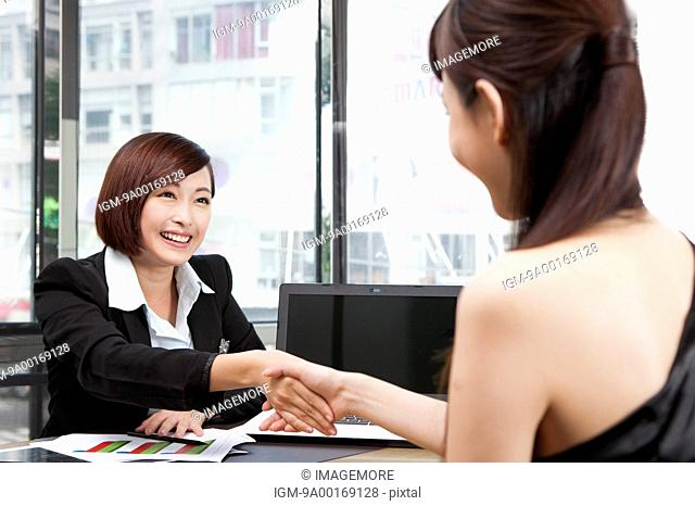 Businesswoman shaking hands and looking away with smile