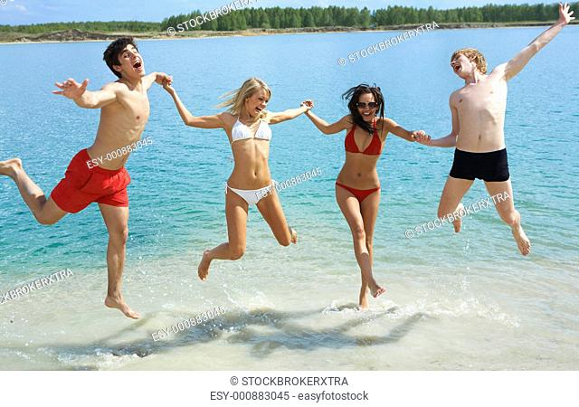 Photo of joyful people holding by hands together and jumping in the lake