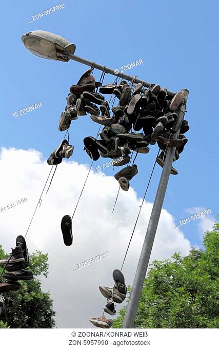 Old shoes at a street lamp