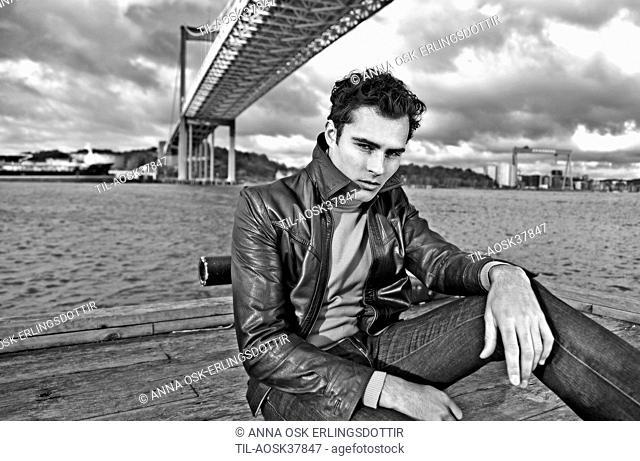 Rugged male figure sitting under bridge wearing leather jacket