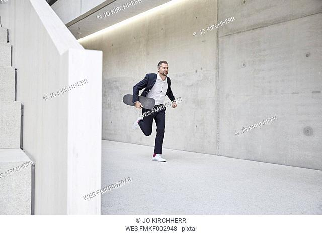 Businesssman running with skateboard along concrete wall
