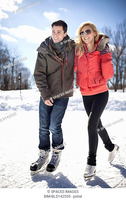 Caucasian couple ice skating on frozen lake