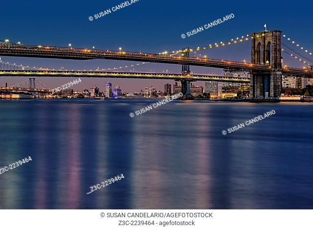 Evening view of New York City's iconic Brooklyn, Manhattan and Williamsburg Bridges. Viewed from the historic area of South Street Seaport in lower Manhattan in...