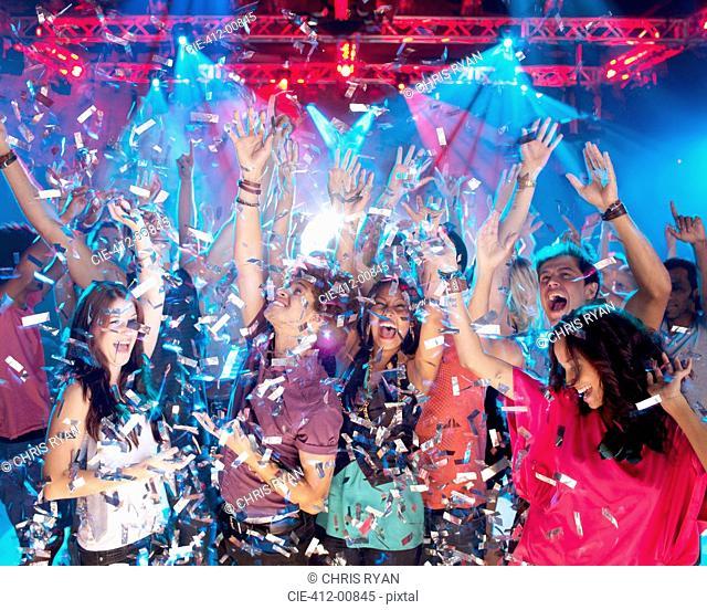 Confetti falling over enthusiastic crowd on dance floor of nightclub