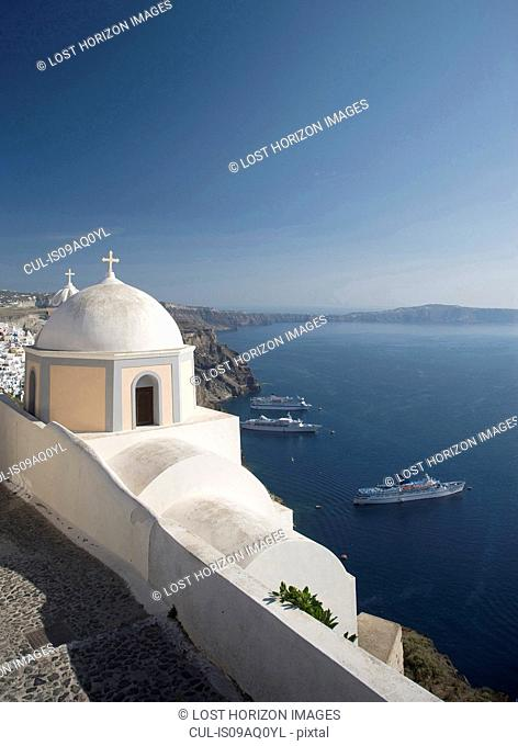 View of white washed church and sea ferries, Oia, Santorini, Cyclades, Greece