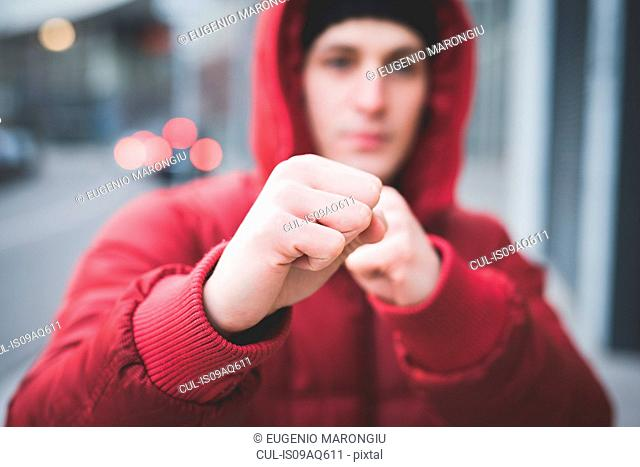 Close up of young mans posing with clenched fists on city street