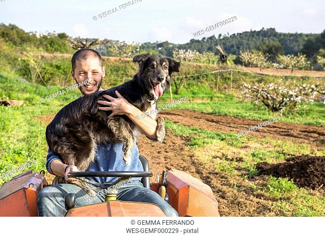 Farmer with tractor on field holding dog