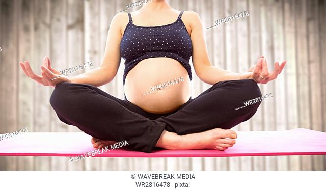 Pregnant woman meditating against blurry wood panel