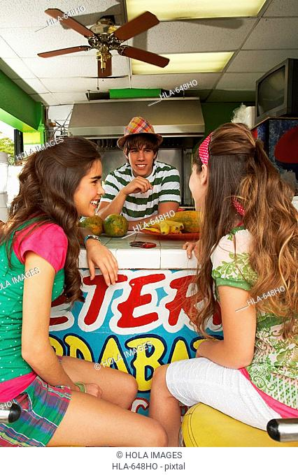 Two teenage girls talking with a bartender in a juice bar