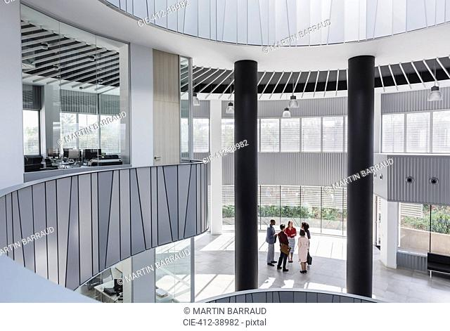 Business people talking in architectural, modern office atrium