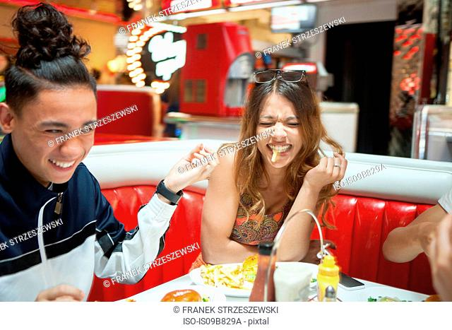 Three young friends sitting in diner, laughing