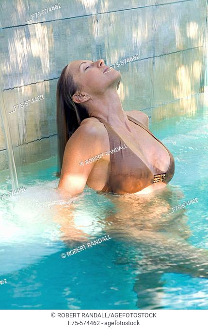 Woman relaxes in pool and rinses her hair in the waterfall