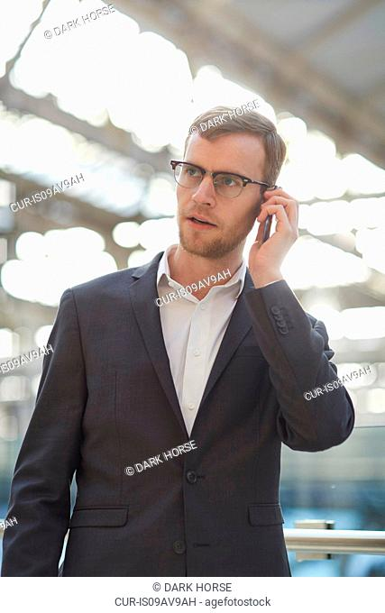 Mid adult businessman using smartphone to make telephone call, looking away