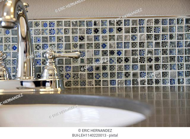 Extreme close-up of shiny faucet with washbasin in the bathroom at home