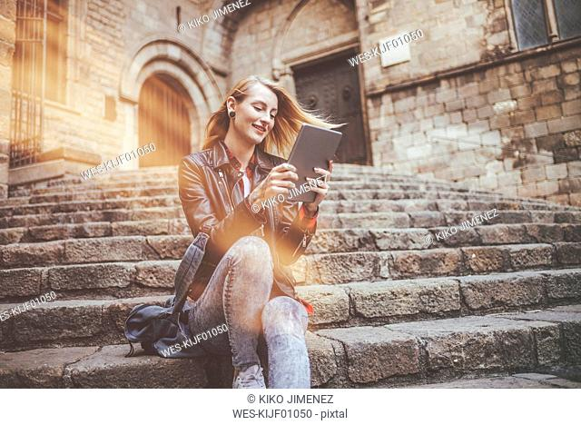 Spain, Barcelona, smiling young woman sitting on stairs looking at tablet
