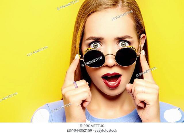 Funny young woman is looking over the sunglasses on a yellow background. Optics, sunglasses