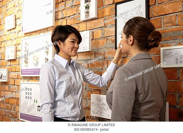Female asian worker showing caucasian female manager print products on wall of printing and packaging factory, China