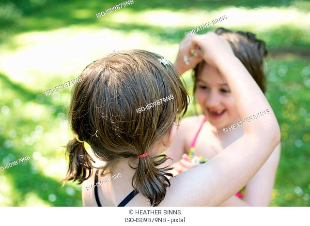 Young girl putting daisies in sister's hair, outdoors