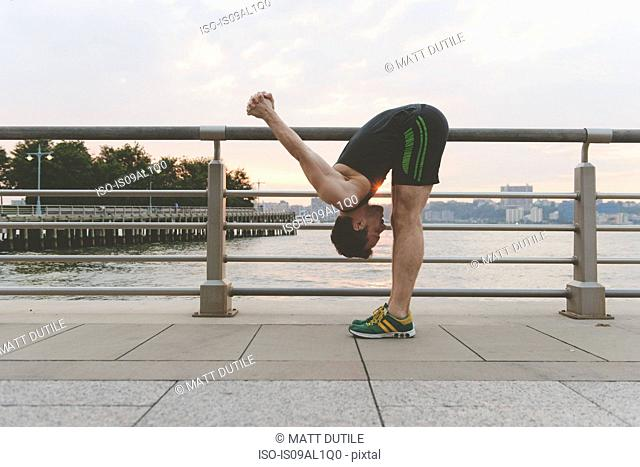 Young man practicing yoga bending down and arms raised at riverside