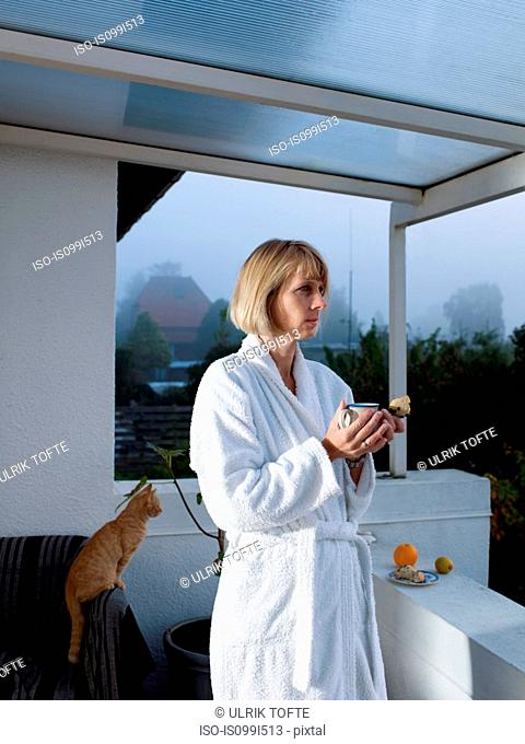 Mature woman in bathrobe holding morning coffee on balcony