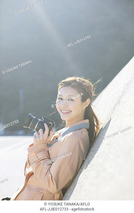Portrait of Japanese woman with camera smiling