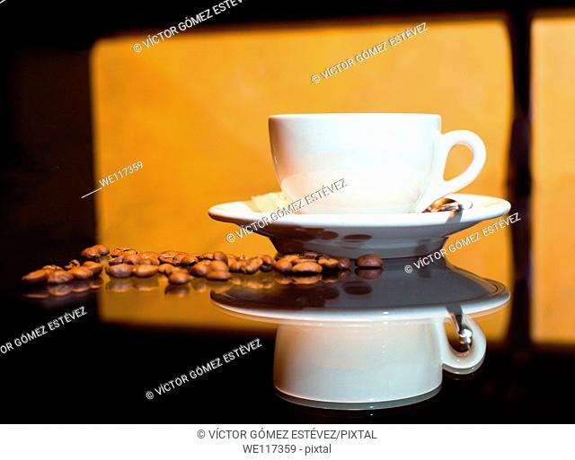 Coffee cup with coffee beans and orange background