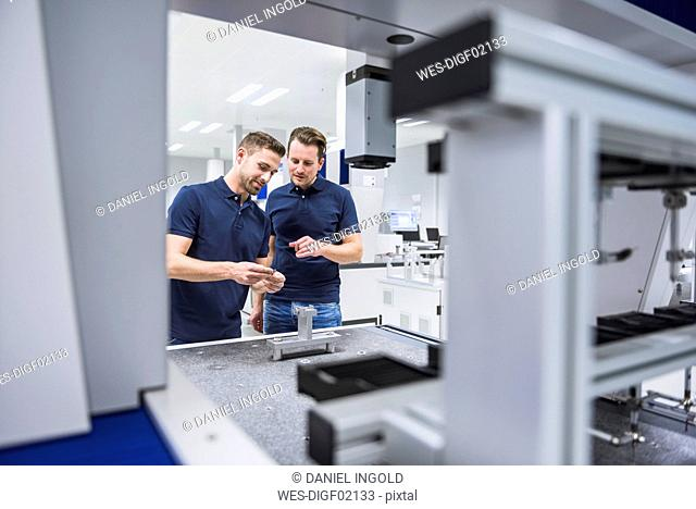 Two men at a machine in testing instrument room