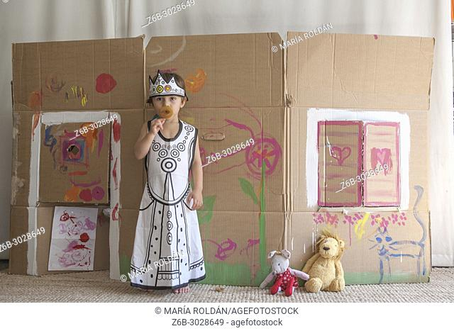 little girl dressed up as a queen in front of a painted carton house