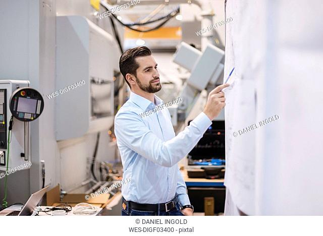 Businessman in factory looking at plan