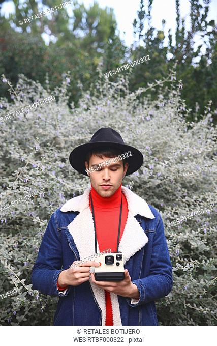 Man holding polaroid camera outdoors