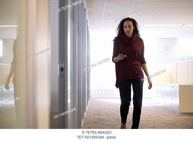 Young woman walking in corridor with mobile phone