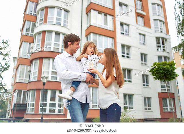 Low angle shot of a young happy family posing in front of new apartment building. Father and mother holding their cute little daughter