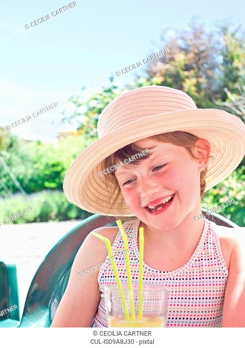 Girl wearing sunhat with soft drink