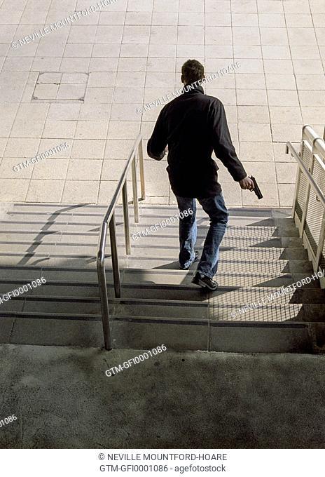 Man walking down steps holding a gun