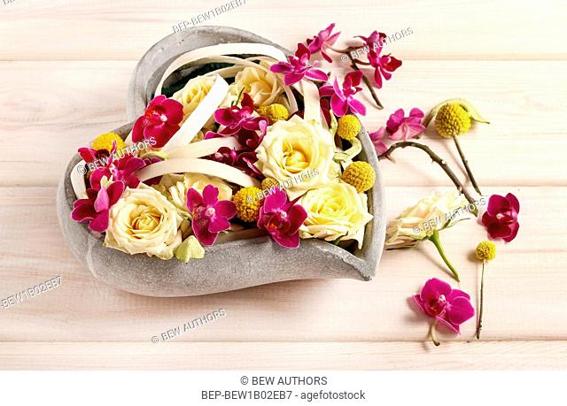 Floral arrangement with roses and orchids in heart shape. Party decor
