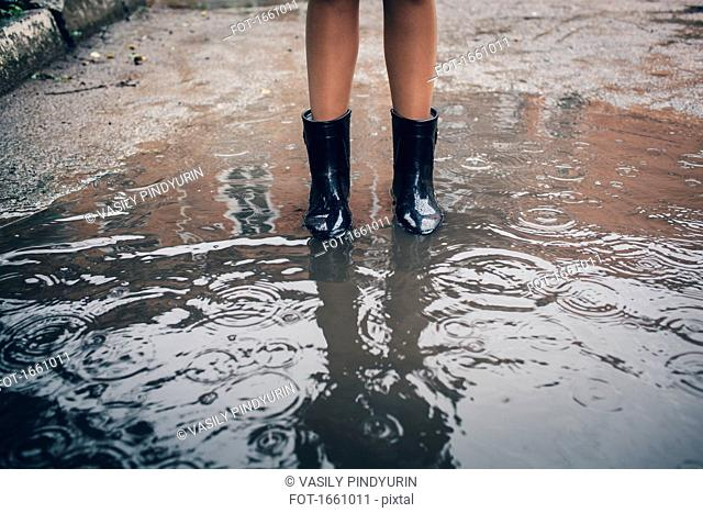 Low section of teenager wearing rubber boot standing in puddle during rain