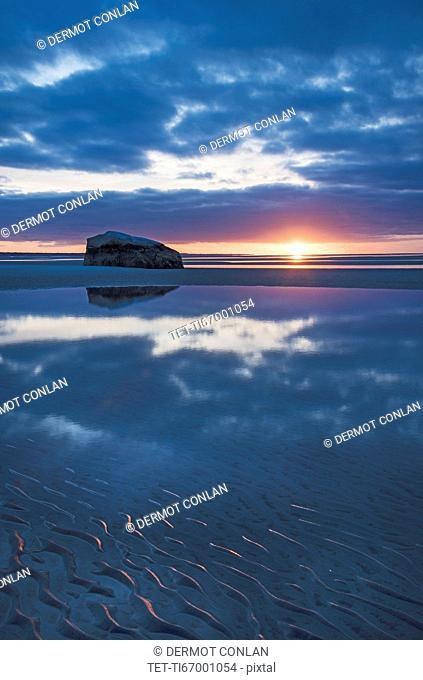 USA, Massachusetts, Cape Cod, Orleans, Rock reflecting in sea at sunset